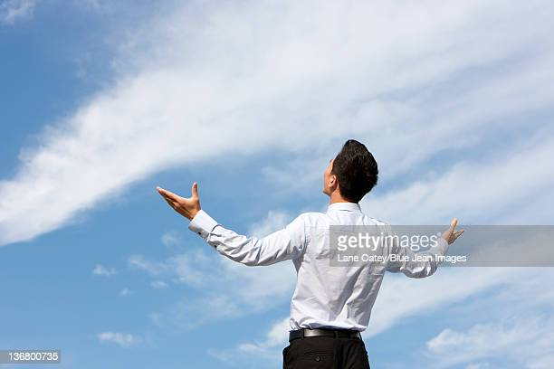 Businessman Standing with Arms Outstretched