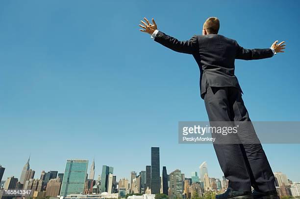 Geschäftsmann, stehend mit Arme sich über die Skyline der Stadt