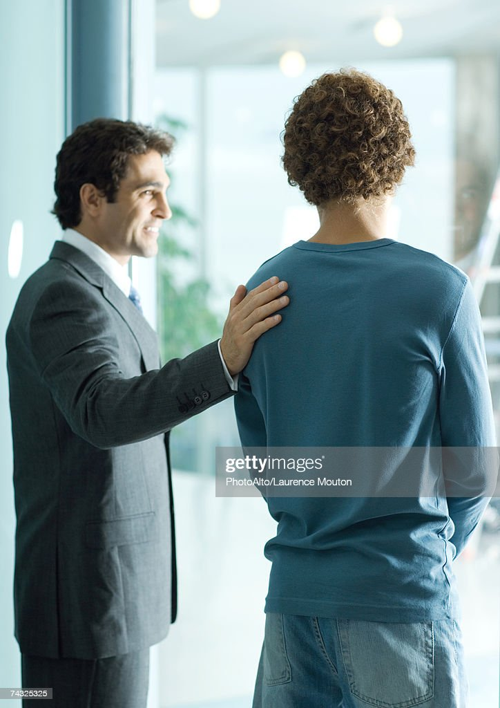Businessman standing with hand on shoulder of casually dressed young man, smiling