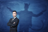 A businessman standing with his hands across and his shadow on a blue empty blackboard behind him with hands overspread, horns and a tail like a devil has. Self-confident behavior. Hidden feelings. In