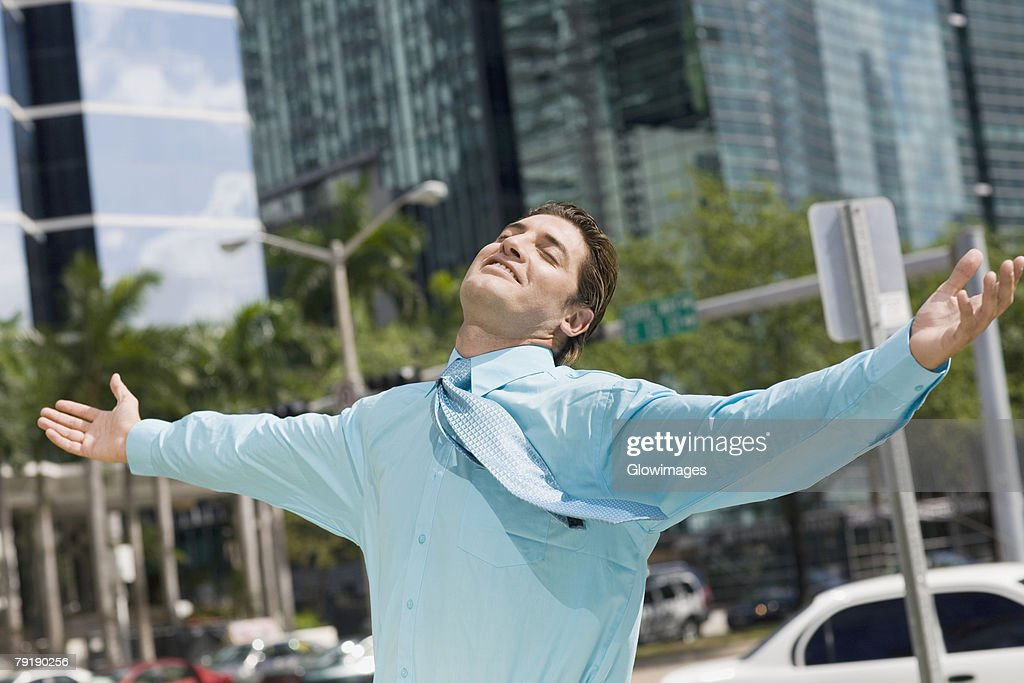 Businessman standing with his arms outstretched : Stock Photo