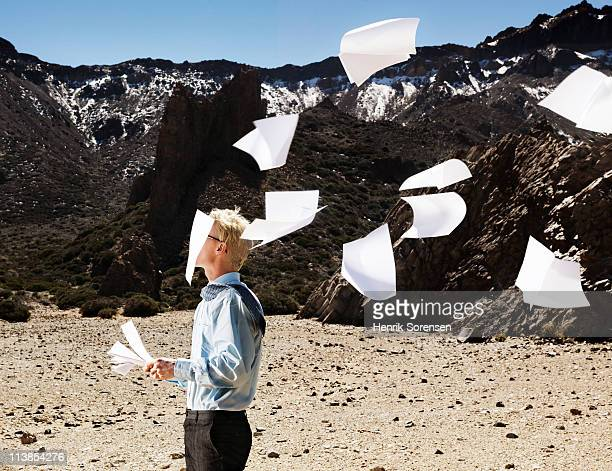 Businessman standing with paperwork blowing away