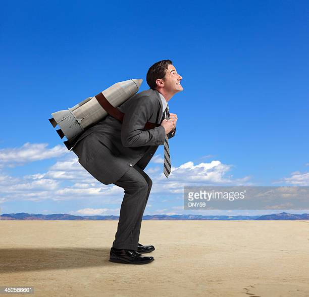 Businessman standing with rocket strapped to his back in desert