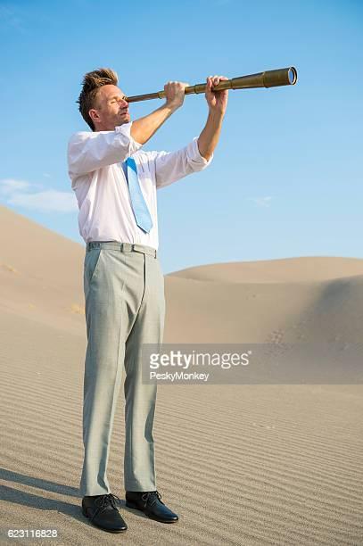 Businessman Standing with Telescope in Desert