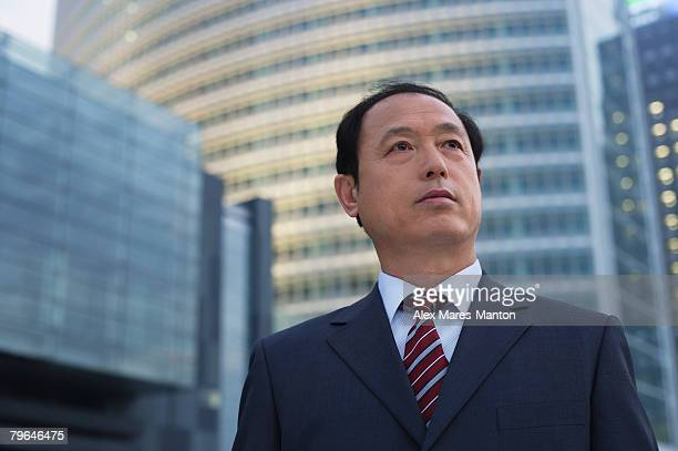 A businessman stands in front of a skyscraper