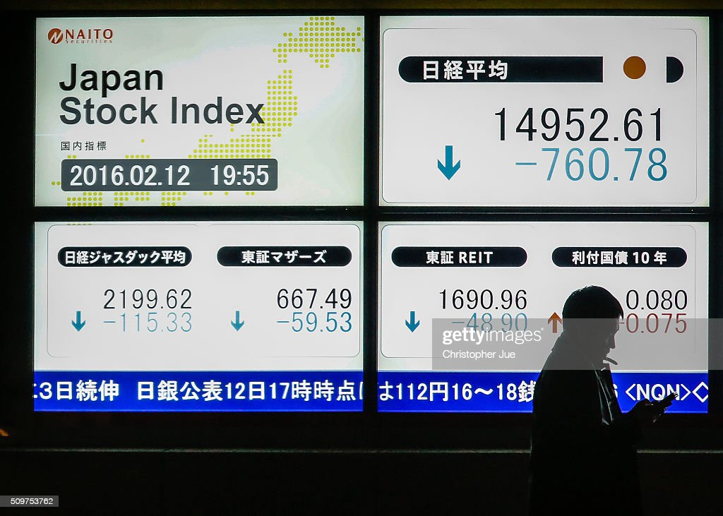 A businessman stands next to a stock market indicator board on February 12, 2016 in Tokyo, Japan. The Nikkei Stock Average finished 11% down for the week, its biggest weekly drop since October 2008, and the index for the day ended 4.8% down, the lowest since October 2014.