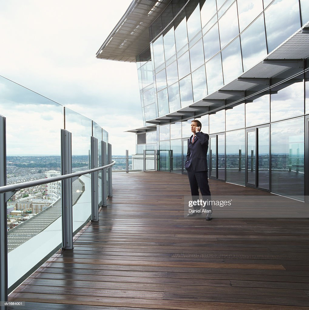 Businessman Stands on the Balcony of an Office Building, Talking on His Mobile Phone : Stock Photo