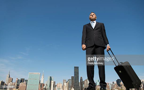 Businessman Stands Tall w Luggage Above Skyline
