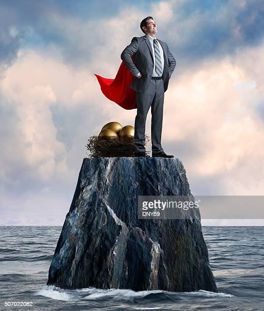 Geschäftsmann steht während der Schutz sein Nest Egg auf einsamen Insel