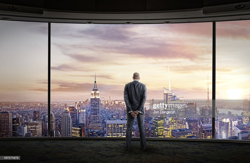 Businessman stares out large windows at city : Stock Photo
