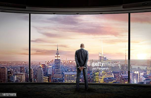Businessman stares out large windows at city