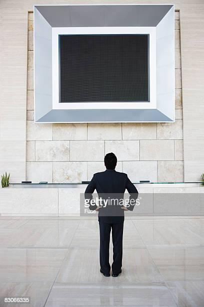Businessman Staring at a Large Monitor