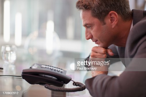 Businessman staring at telephone waiting for it to ring