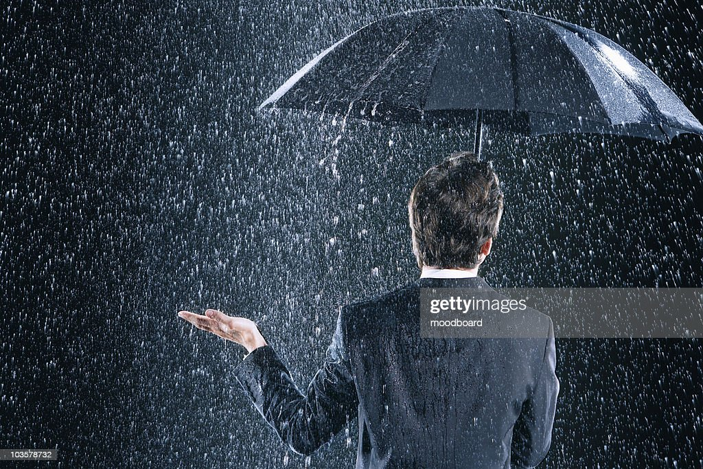 Businessman staying dry under umbrella during downpour, back view : Stock Photo