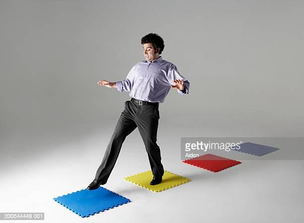 Businessman stepping across puzzle pieces, studio shot