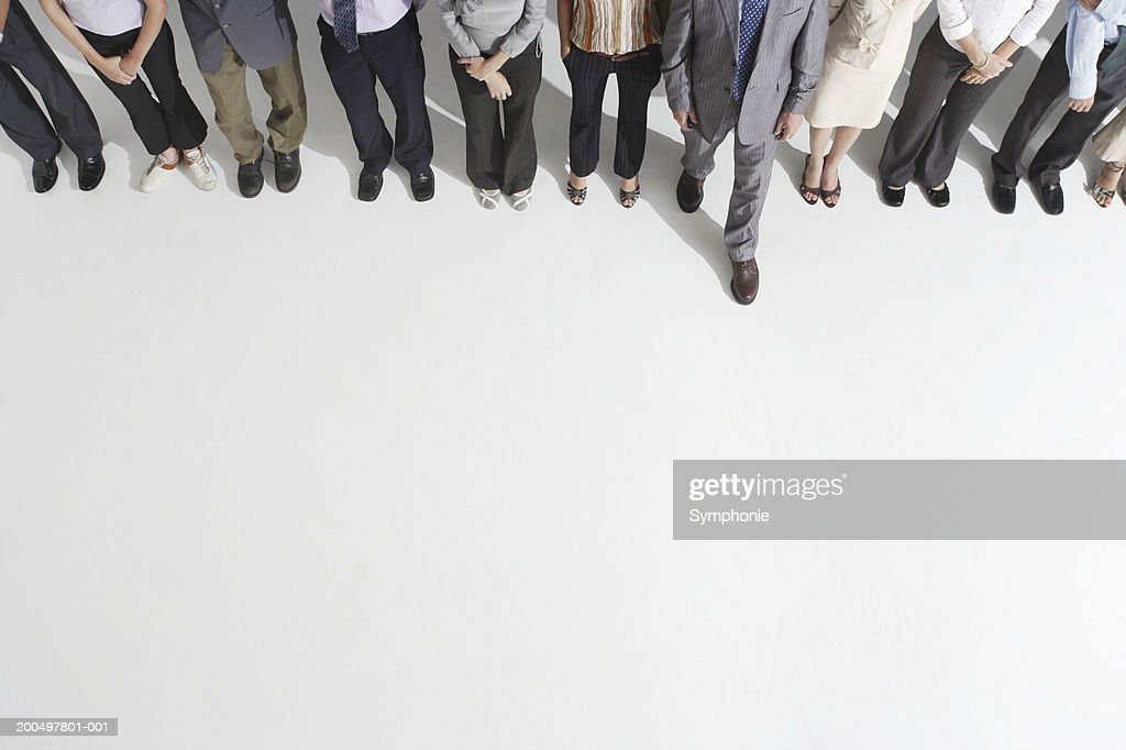 Businessman stepping forward from line of colleagues, low section : Stock Photo