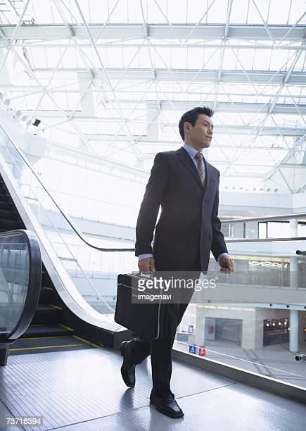 Businessman stepping off escalator