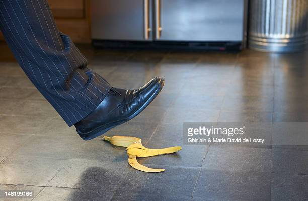 Businessman stepping on banana peel