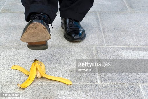 Businessman stepping on banana skin, copy space : Stock Photo