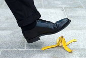 Businessman stepping on banana skin