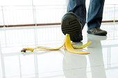 Businessman stepping on banana skin in office building hall.