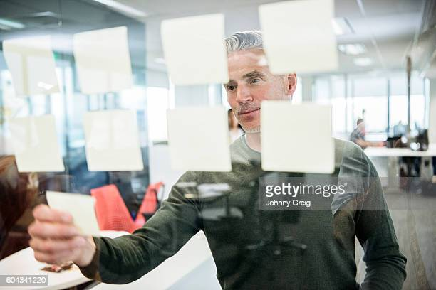 Businessman sticking notes on window in office