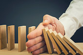 Businessman halting the domino effect inserting his hand between falling and upright wooden blocks