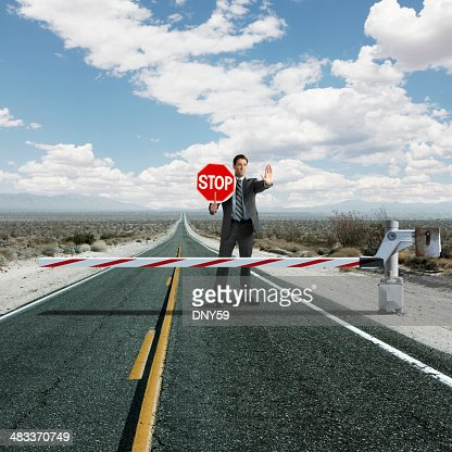 Businessman stopping traffic at roadblock