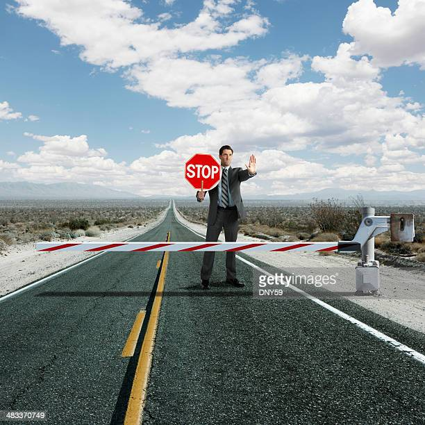 Businessman stopping traffic at roadblock