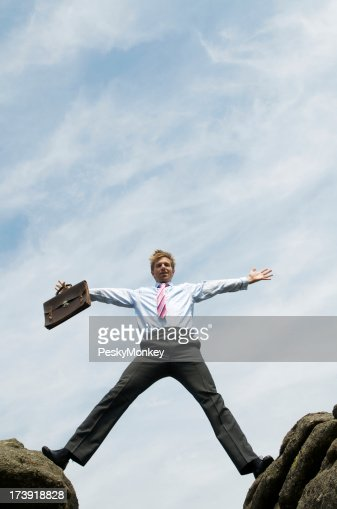 Businessman Straddles the Gap between Rocks