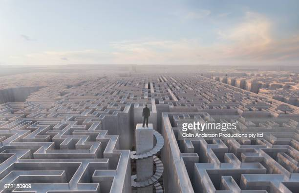 Businessman stranded at top of complex maze