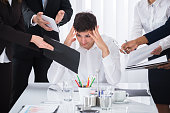 Young Businessman Stressed Out At Work Surrounded By Businesspeople