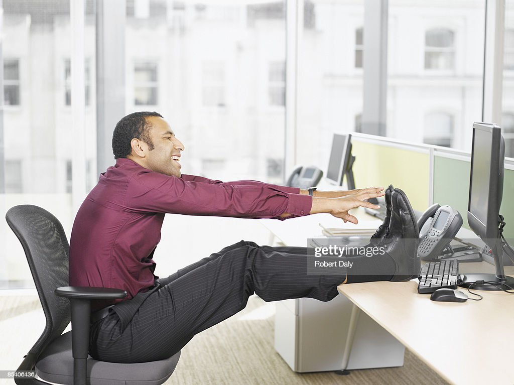 Businessman stretching at desk : Stock Photo