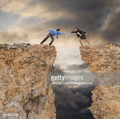 Businessman stretching to help co-worker across cliff gap