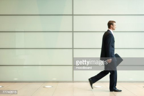 Businessman Striding Down Office Corridor