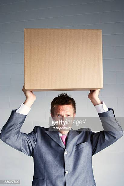 Businessman Struggles Holding Box Over His Head