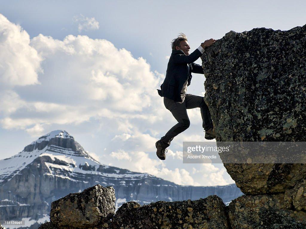 Businessman struggles to climb summit. : Stock Photo