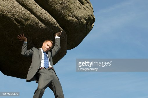 Businessman Struggling Lifting Massive Boulder Outdoors in Sky