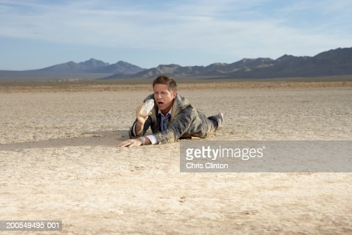 Businessman Struggling On Dry Lake Bed Holding Empty Water ...