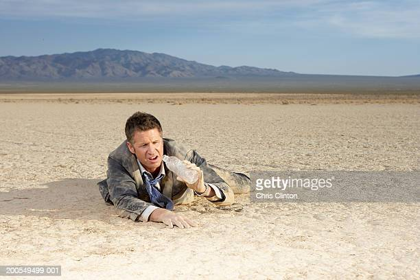 Businessman struggling on dry lake bed, looking at empty water bottle
