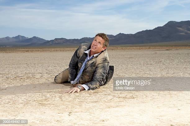 Businessman struggling on dry lake bed, looking upwards