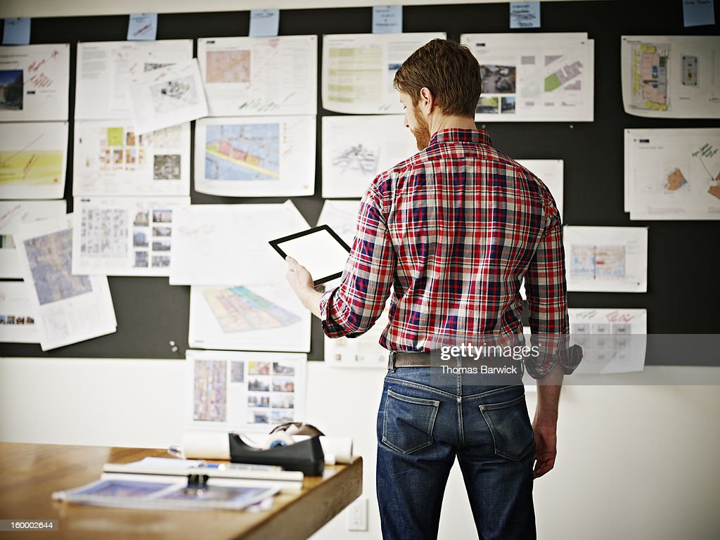 Businessman studying digital tablet in office : Stock-Foto
