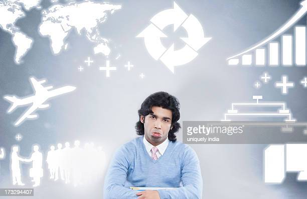Businessman sulking sitting in front of a background of various business icons