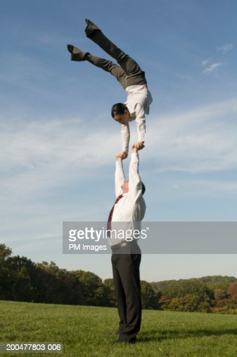 Businessman supporting woman doing handstand : Stock Photo