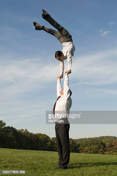 Businessman supporting woman doing handstand