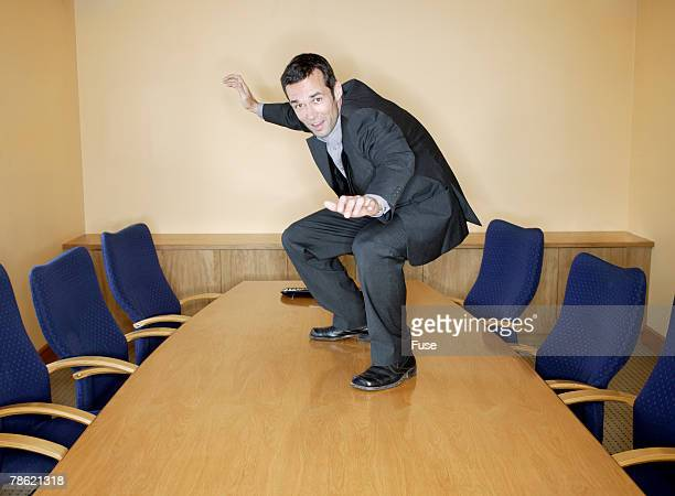 Businessman Surfing on Conference Table