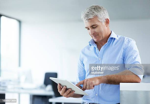 Businessman surfing the internet on his tablet