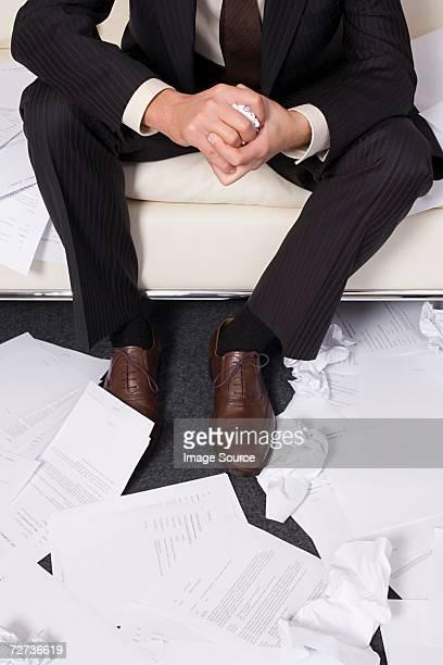 Geschäftsmann umgeben von Faltig Weißbuch