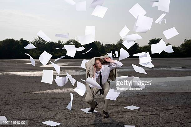 Businessman surrounded by swirling papers (composite)