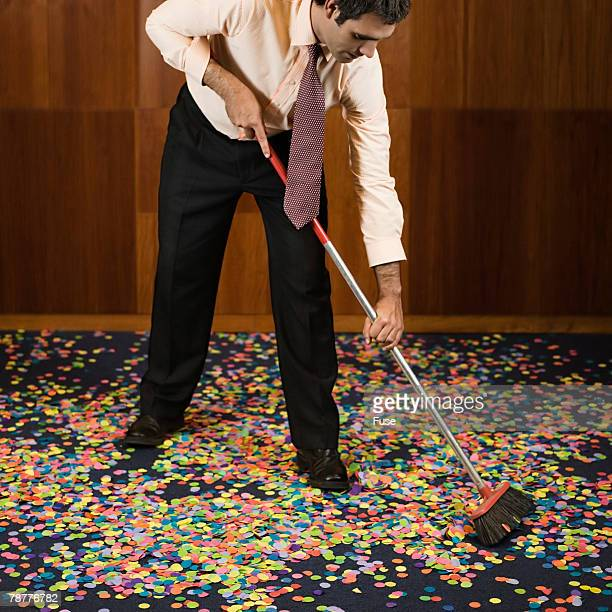 Businessman Sweeping up Confetti